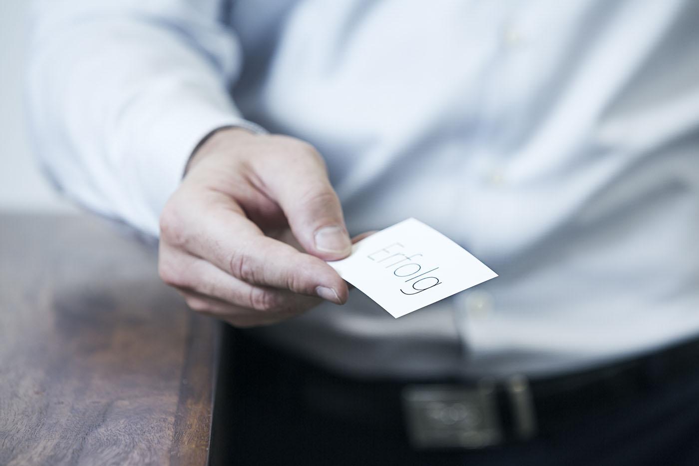 Mann mit Visitenkarte von Martina Schwarzer fotografiert